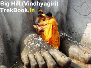 Jain pilgrims performing  abhishek on Gometshwars charan